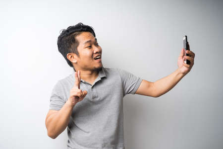 Portrait of young Asian man, taking self-portrait photograph or selfie isolated and selective focus.