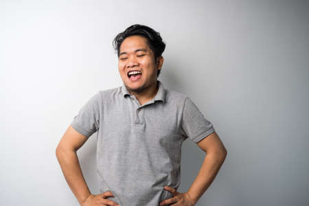 Portrait of young Asian man, smile akimbo standing. Isolated selective focus Stock Photo