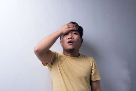 Portrait of Young Asian man with face expression, shocked, pointing finger, disappointment, weird and wow. Isolated background. Copy space, selective focus Stock Photo