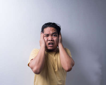 Face reaction, Asian young man portrait of face expression, shocked, thrilled, scared, surprised, with covered face with hand. Isolated, selective focus, copy space