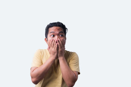 Face reaction, Asian young man portrait of face expression, shocked, thrilled, scared, surprised, with covered face with hand. Isolated, selective focus, copy space Stock Photo
