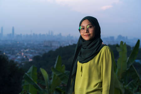 Portrait of young Asian woman during sunset, blue hour at hill view point, Bukit Ampang near Kuala Lumpur. Blurred background