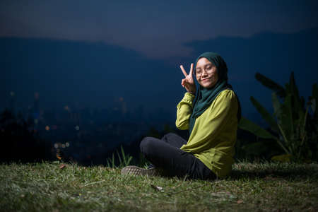 Pretty girl sitting on grass, relaxing, enjoying Kuala Lumpur city view during sunset. Portrait of young Asian woman, wearing hijab and green attire.