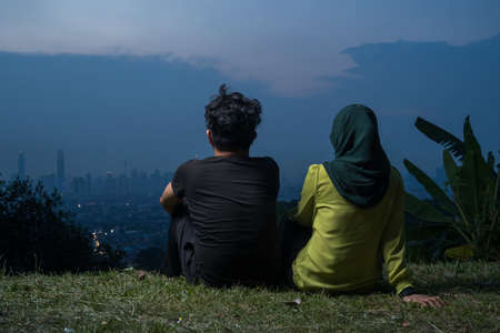 Portrait of Young Asian couple, man and woman, sitting on grass enjoying Kuala Lumpur view during blue hour.