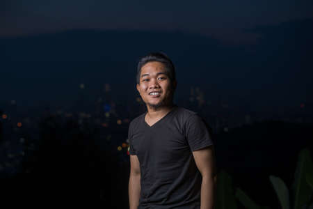 young asian man, lifestyle portrait during night.