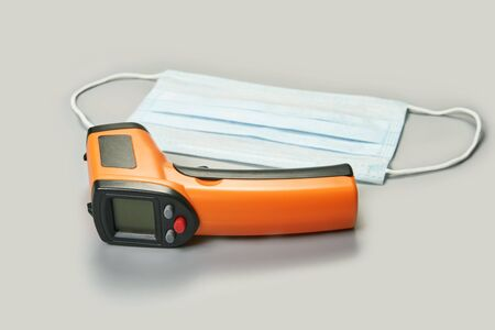 ir scanner thermometer and blue surgical medical mask