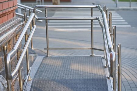 Ramp way with stainless steel handrail with for support wheelchair disabled people. accessibility architecture fo low mobile people.