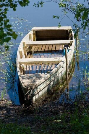 Shabby boat On the bank of lake photo