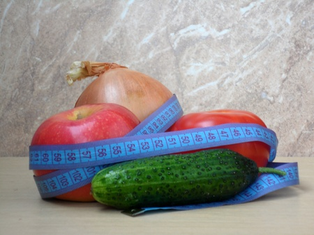apple, tomato, cucumber, onion girded with a tailor measuring tape