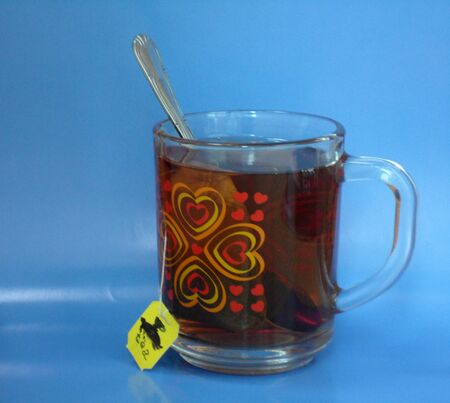 slow tea bags in a clear glass mug with cartoon pattern on a blue background Stock Photo