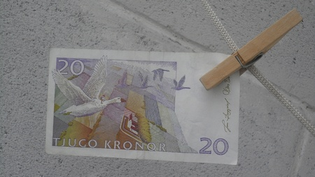 The Swedish note 20 kroons hanging back on a clothesline on a background of a concrete wall  Stock Photo