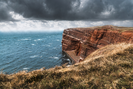 Mountain formation at the coast of Helgoland in the German north sea. View from the grass cliff. Strong wind going by with heavy clouds. Perfect travel destination with cooler weather conditions.