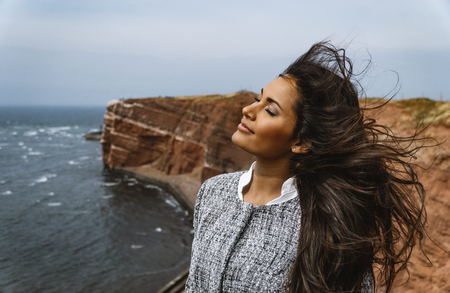 Beautiful young model posing in front of the Lange Anna in Helgoland Northern Germany with the wind going through her long hair.