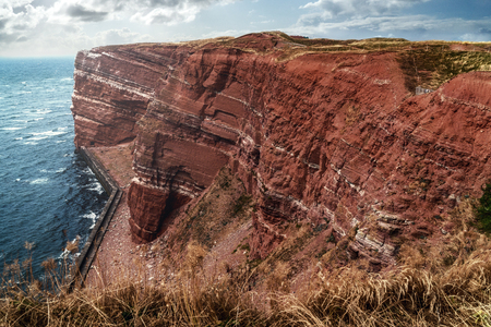 Mountain cliff formation at the coast of Helgoland in the German north sea covered by sun streams. Strong wind going by with heavy clouds. Perfect travel destination with cooler weather conditions.