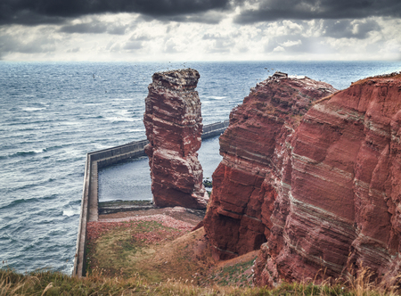 Mountain cliff formation Lange Anna at the coast of Helgoland in the German north sea.Viewed from a grass edge. Strong wind going by with heavy clouds. Perfect travel destination with cooler weather.