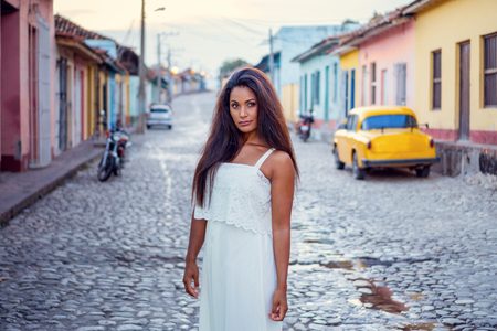 Beautiful dark skinned young lady in white dress standing in front of an old classic car and a motorcycle in the old streets of Trinidad in Cuba.