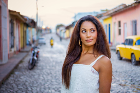 Beautiful dark skinned young lady in white dress standing in front of an old classic car and a motorcycle in the old streets of Trinidad in Cuba looking sideways.