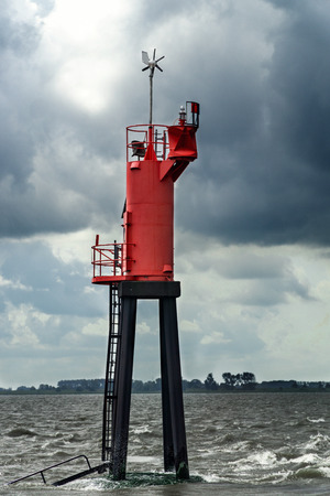 A big red buoy as a navigational marker in the Northern Sea in Germany.