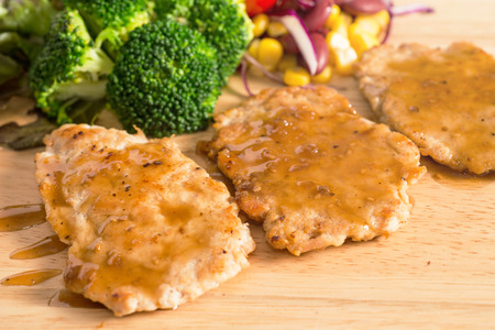 Pork cube steak topped with pepper sauce and creamy salad on wood plate Standard-Bild