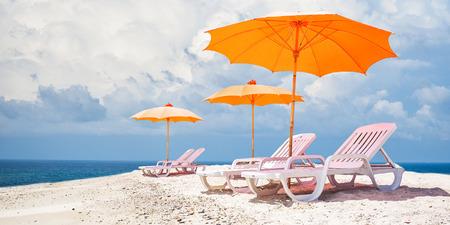 orange chairs: Orange beach umbrellas and chairs Stock Photo