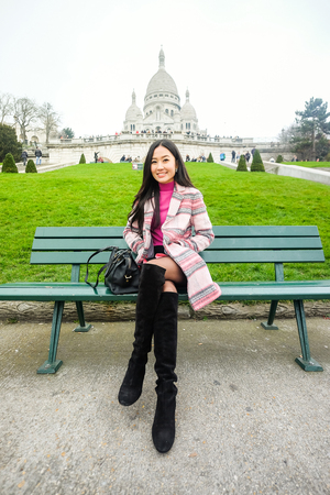Asian beautiful girl sitting on a bench near the Sacre-Coeur in Paris Stock Photo