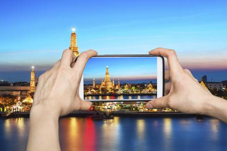 wat arun: Girl taking pictures on mobile smart phone in Wat Arun,bangkok, Thailand