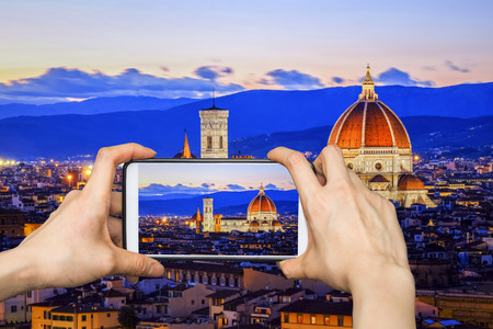 Girl taking pictures on mobile smart phone in Duomo View of Florence after sunset from Piazzale Michelangelo, Florence, Italy Stock Photo