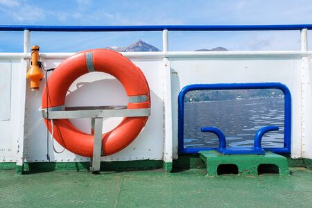 Lifebuoy in front of the blue sea and the white ship  Stock Photo