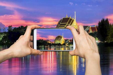 Taking pictures on mobile smart phone in Sunset in Wat That at bueng kaen nakhon lake khon kaen Thailand