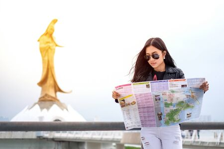 kaew: MACAU - JANUARY 11, 2016: Young female tourist with map looking for a way to Statue of kun iam in Macau. It is a popular tourist attraction of Asia.