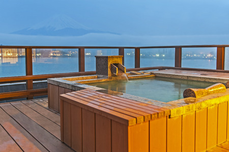 Japanese open air hot spa onsen with view of the mountain Fuji Stock Photo