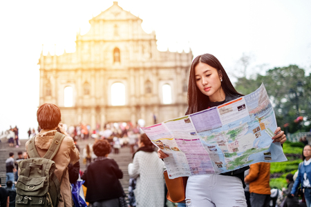 MACAU - JANUARY 11, 2016: Young female tourist with map looking for a way to View of the Ruins of St. Pauls Cathedral in Macau. It is a popular tourist attraction of Asia. Stock Photo