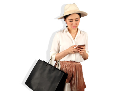 Young asian woman to see a smartphone and hold shopping bag