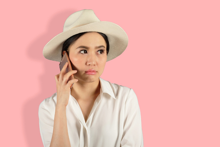 young attractive asian woman waiting answer for a smart phone on Pink backgroud Stock Photo