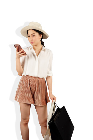 Young asian woman to see a smartphone and hold shopping bag in white background
