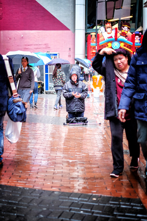 unneeded: Hong Kong January 15 2016 : People passing a homeless man praying on the street on the rainy day in Hong Kong city in 15 Jan 2016