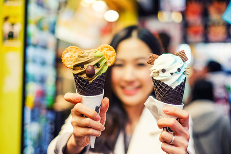 Asian young female model eating ice cream cone on Hong Kong Street Standard-Bild