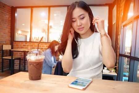 Young woman listening to music in coffee shop Stock Photo