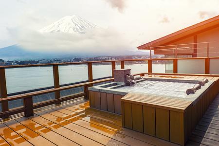 Spa al aire libre japonés onsen caliente con vista a la montaña Fuji