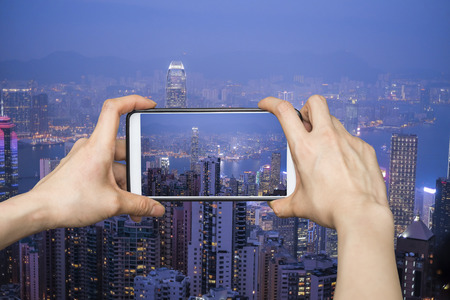 hight tech: Girl taking pictures on mobile smart phone in HongKong cityscape at night , Hong kong city.