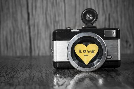 Old retro camera with heart love in wood background