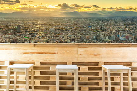 wooden table or counter and chair isolated on cityscape view in the morning background