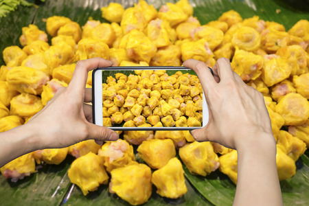 Girl taking pictures on mobile smart phone in Chinese Steamed Dumpling on banana leaf in Fresh maket Stock Photo