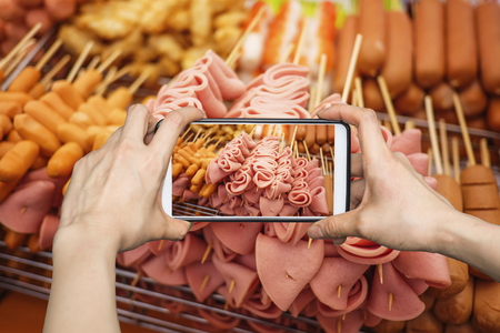 Girl taking pictures on mobile smart phone in Meat ball, Sausage and ham on a stick