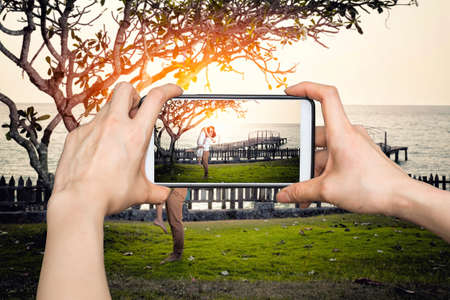 old photograph: Girl taking pictures on mobile smart phone Happy couple relaxing in a tree by the sea