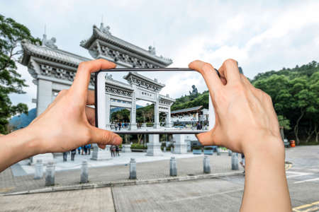 hight tech: Girl taking pictures on mobile smart phone in Front View of Tian Tan Giant Buddha in blue sky