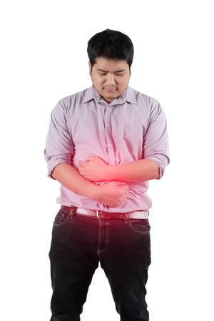 sigmoid colon: a man holding his hands over the lower abdominal because of suffering from stomach ache Stock Photo