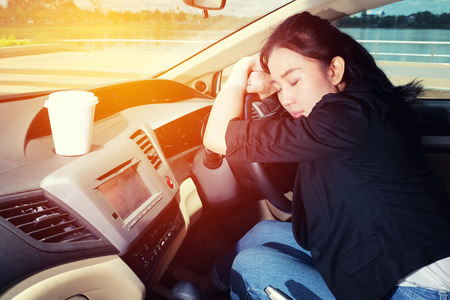 Tired young woman asleep in her car Stock Photo