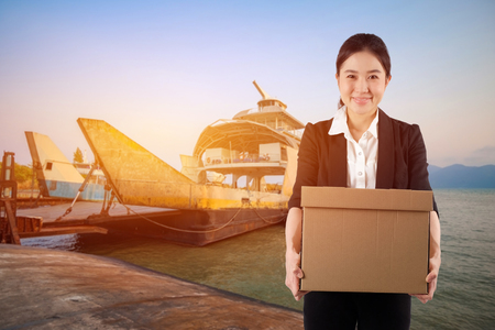 A young woman carrying a box wtih smiling on Cargo Ship background