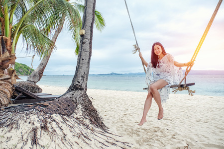 Beautiful woman sitting on a swing on the beach in Koh Phangan, Thailand